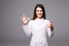 Gladlynt attraktiv doktor för ung kvinna som rymmer en preventivpiller och visar tummar upp över grå bakgrund royaltyfri bild