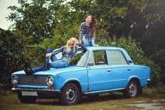 Gladlynt attraktiv flicka och brunett för två barn som blond poserar på huven av en gammal rostig bil, en iklädd jeans och skjort arkivbild