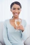 Gladlynt attraktiv kvinna som dricker vitt vin Arkivbild