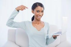 Gladlynt attraktiv kvinna som pekar på hennes bärbar dator Royaltyfri Fotografi