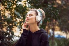 Gladlynt attraktiv ung flicka i hoodie och kulöra dreadlocks royaltyfria foton