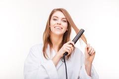 Gladlynt attraktiv ung kvinna som rätar ut hennes hår med straighteneren Royaltyfri Foto