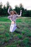 Gladlynt banhoppning för ung kvinna på ängen royaltyfri fotografi