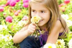 Gladlynt barn med blommor Arkivbild