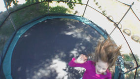 Gladlynt barnbanhoppning på trampolinen arkivfilmer