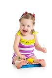 Gladlynt behandla som ett barn flickan som spelar med den musikaliska leksaken Royaltyfria Bilder
