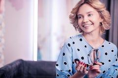Gladlynt blåögd kvinna som ler stund genom att använda framsidapulver fotografering för bildbyråer