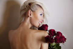 Gladlynt blond kvinna med blommor Royaltyfri Fotografi