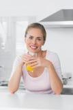 Gladlynt blond kvinna som har orange fruktsaft Fotografering för Bildbyråer