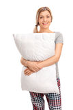 Gladlynt blond kvinna som kramar en kudde Arkivfoton