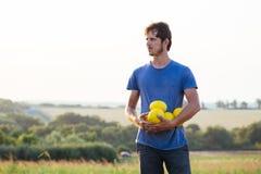 Gladlynt bonde som rymmer den nya melonskörden på fältet på den organiska ecolantgården arkivfoto