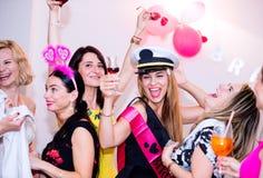 Gladlynt brud och brudtärnor som firar möhippan med drinkar arkivfoto