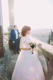 Gladlynt brud och hennes lycklig ny make som poserar på balkongen av den gamla gotiska domkyrkan Royaltyfri Bild