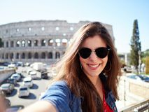 Gladlynt brunett i solglasögon som ler på kameran arkivfoton