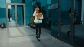 Gladlynt brunettkvinna i exponeringsglas med böcker i händer stock video