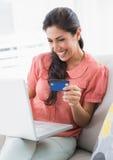 Gladlynt brunettsammanträde på hennes soffa genom att använda bärbara datorn för att shoppa onlin Arkivfoton