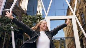 Gladlynt caucasian flicka med långt hår i lyckligt gå för stilfulla exponeringsglas ner stadsgatan nära exponeringsglasbyggnadsst lager videofilmer
