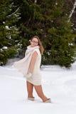 Gladlynt Caucasian ung kvinna som poserar i snöig vinter Arkivbild