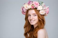 Gladlynt charmig kvinna i blommakrans över grå bakgrund Royaltyfri Bild