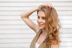 Gladlynt charmig ung kvinna med ett underbart leende med lockigt blont hår i stilfullt posera för waistcoat royaltyfria bilder