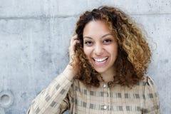 Gladlynt dig kvinna som skrattar med handen i hår royaltyfri fotografi