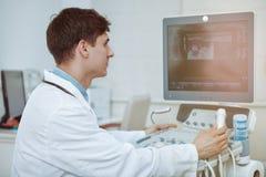 Gladlynt doktor som använder ultraljudbildläsaren på arbete royaltyfri bild