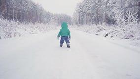Gladlynt en årspojke i vinterskogen som skapas med gimbalen lager videofilmer