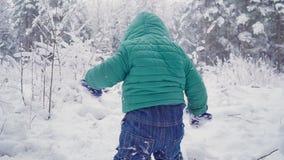 Gladlynt en årspojke i vinterskogen som skapas med gimbalen arkivfilmer