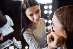 Gladlynt förtjust makeupkonstnär som använder mascara Royaltyfri Bild