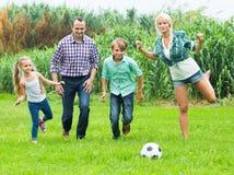 Gladlynt familj av fyra som spelar i fotboll Fotografering för Bildbyråer