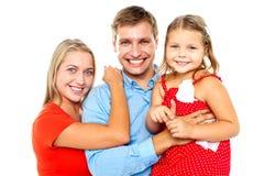 Gladlynt familj av vändande mot kamera tre och att le Arkivbilder