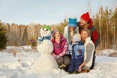 Gladlynt familj med snögubben Arkivbild