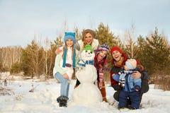 Gladlynt familj med snögubben Arkivfoton