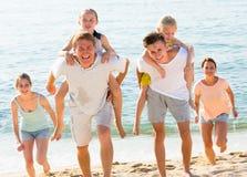 Gladlynt familj på Sandy Beach Arkivbilder