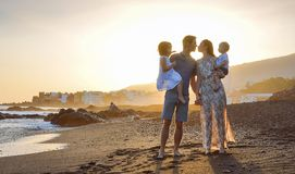 Gladlynt familj som går på den tropiska stranden arkivfoto