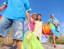 Gladlynt familj som går till stranden Arkivbilder