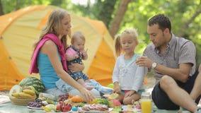 Gladlynt familj som har picknicken med frukter