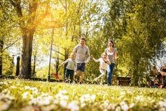 Gladlynt familj som spelar med deras barn` s arkivbilder