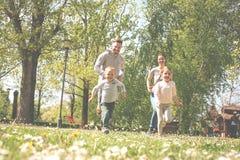 Gladlynt familj som spelar med deras barn` s i ängen arkivfoto