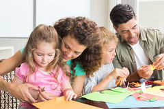 Gladlynt familj som tillsammans gör konsthantverk på tabellen Arkivbild
