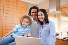 Gladlynt familj som tillsammans surfar internet i kök Royaltyfria Foton
