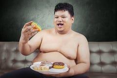 Gladlynt fet man som äter donuts Royaltyfria Bilder