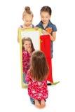 Gladlynt flicka framme av en spegel Arkivbild