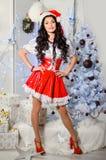 Gladlynt flicka i den Santa Claus hatten Garneringar för nytt år, gåva Arkivfoto