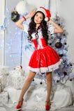 Gladlynt flicka i den Santa Claus hatten Garneringar för nytt år, gåvor Royaltyfria Bilder
