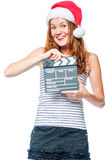Gladlynt flicka i den santa hatten med clapperfilmen i händer på vit Fotografering för Bildbyråer
