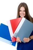 Gladlynt flicka i en blå klänning med mappar för dokument royaltyfri bild