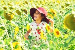 Gladlynt flicka i en bredbrättad hatt som spelar i fältet med solrosor royaltyfri foto