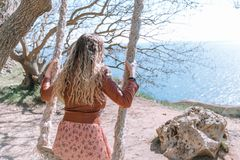 Gladlynt flicka i en klänningridning på en gunga som förbiser havet royaltyfria bilder