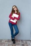 Gladlynt flicka i exponeringsglas som poserar och ler krama bärbara datorn Arkivbild